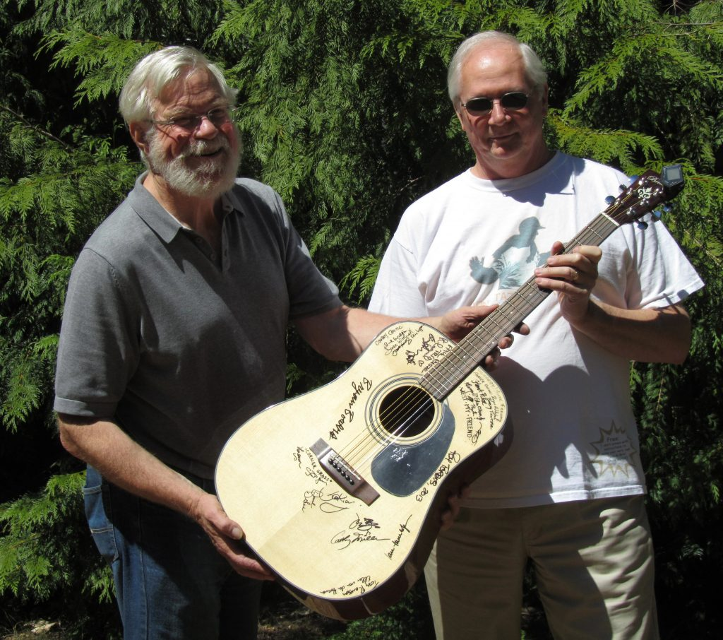 The winner of the 2012-2013 guitar raffle, Paul Bulmer, receiving his prize from Bob de Wolff.